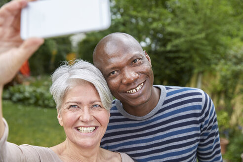 Portrait of smiling couple taking selfie with smartphone - FMKF002735