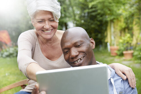 Portrait of smiling couple in the garden looking at tablet - FMKF002738