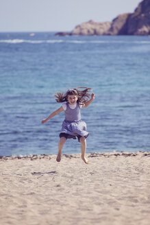 Spain, happy little girl jumping in the air on the beach - XCF000094