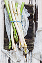 Tied green and white asparagus on old wooden board - SBDF002939