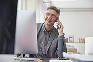 Mature businessman working in office, talking on the phone - RHF001482