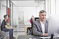 Mature businessman and coworkers working in office - RHF001494