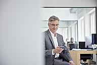 Mature businessman in office using smart phone - RHF001524