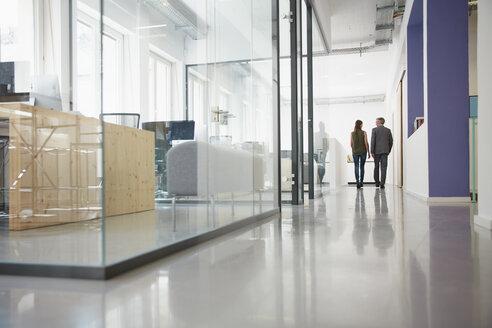 Businessman and woman walking down office corridor - RHF001557