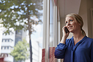 Businesswoman standing by window, talking on the phone - RHF001581