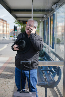 UK, Bristol, portrait of laughing senior man telephoning with smartphone while waiting at bus stop - JCF000008