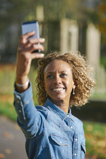 Portrait of smiling woman taking selfie with smartphone - JCF000018