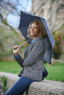 Portrait of smiling woman with umbrella - JCF000021