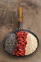 Pan with chia, dried wolfberries and quinoa on wood - ODF001388
