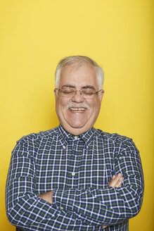 Portrait of smiling senior man with arms crossed and eyes closed in front of yellow background - JCF000031