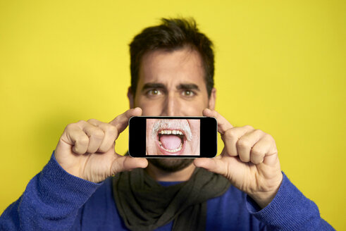 Portrait of man holding smartphone with photography of another man's screaming mouth - JCF000034