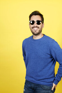 Portrait of smiling man wearing sunglasses in front of yellow background - JCF000037