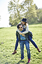 Man giving woman a piggyback ride on a meadow - JCF000052