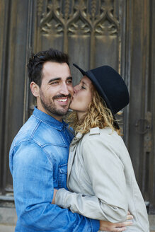 Woman kissing smiling man - JCF000055
