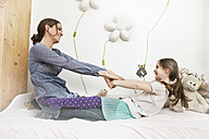Mother playing with her little daughter on bed - MFF002988