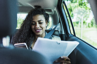 Smiling young woman in car with folder and cell phone - UUF007476
