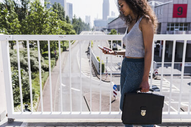 Young woman on bridge looking at cell phone - UUF007503