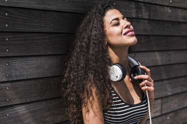 Relaxed young woman with headphones leaning against wooden wall - UUF007554