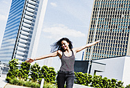Enthusiastic young woman with outstretched arms outdoors - UUF007560