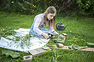 Girl playing 'cooking' with herbs on a meadow - SARF002732
