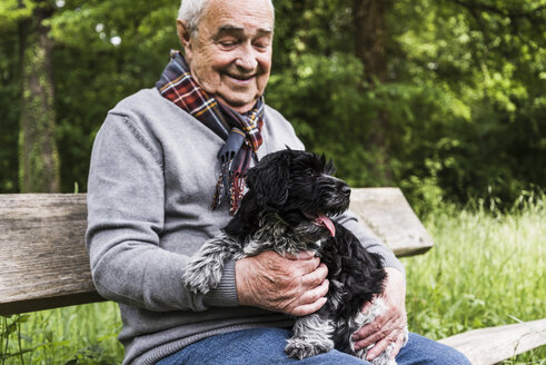 Smiling senior man sitting with his dog on a bench in nature - UUF007567