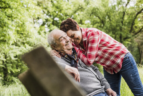 Happy woman hugging her old father sitting on a bench in nature - UUF007570