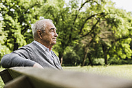 Smiling senior man sitting on a bench in nature - UUF007576