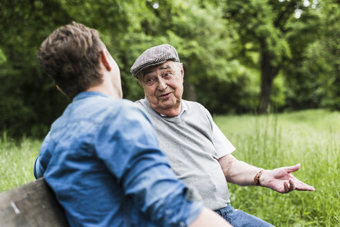 Portrait of senior man sitting on a bench talking to his grandson - UUF007597