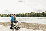 Senior man strolling with his daughter at riverside - UUF007606