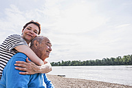 Adult daughter hugging her father at riverside - UUF007615