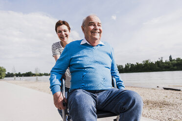 Woman pushing her old father sitting on wheeled walker - UUF007621