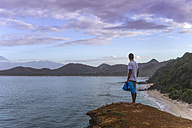 Indonesia, Sumbawa island, Young man standing on viewpoint - KNTF000297