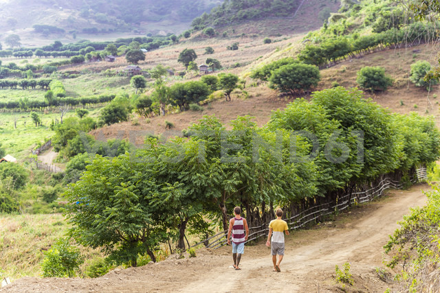 Indonesia, Sumbawa island, Two young men walking on a dirt road - KNTF000303