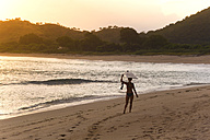 Indonesia, Sumbawa island, Surfer girl at the beach in the evening - KNTF000306