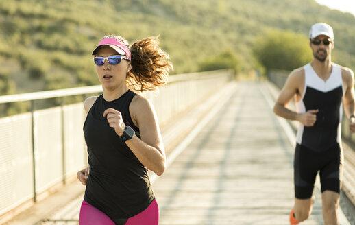 Two athletes running on a bridge - JASF000737