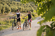 Sportive man and woman pushing bicycles and talking in rural landscape - JASF000743