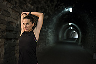 Sportive woman stretching in a tunnel - JASF000755