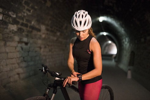 Sportive woman with bicycle looking at smartwatch in a tunnel - JASF000758