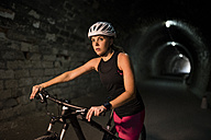 Sportive woman with bicycle in a tunnel - JASF000761
