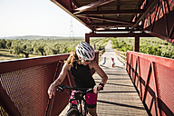 Sportive woman on bicycle looking at smartwatch on a bridge - JASF000767