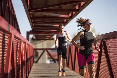 Two athletes running on a bridge - JASF000773