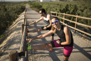 Smiling sportive woman and man stretching on a bridge - JASF000776
