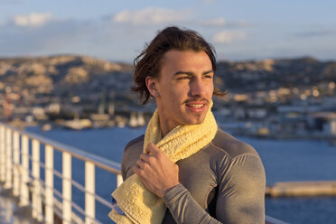 Portrait of young man with towel standing on deck of a cruise ship - ONBF000047