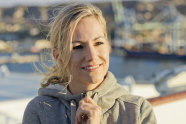 Portrait of smiling blond woman on deck at sunlight - ONBF000050