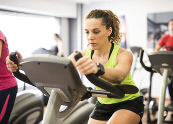 Woman training on exercise bike in gym - JASF000787
