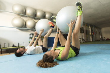 Woman and man exercising with fitness balls in gym - JASF000790