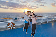 Group of friends taking selfies on a cruise - ONBF000051