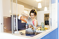 Young woman in kitchen pouring smoothie into mug - JRFF000735