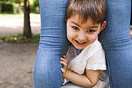 Portrait of happy boy between mother's legs - VABF000534