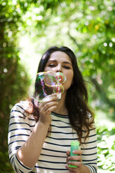 Young woman blowing soap bubbles - VABF000546